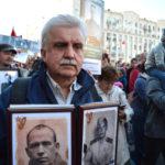 Ein Teilnehmer trägt die Fotografien seiner Vorfahren.