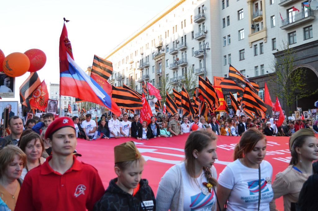 Ein übergroßes Banner des Unsterblichen Regimentes tragen die Teilnehmer durch die Stadt.